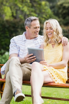 Happy couple using tablet on a bench outside