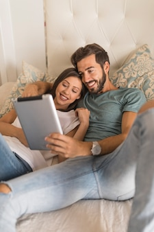 Happy couple using tablet on bed