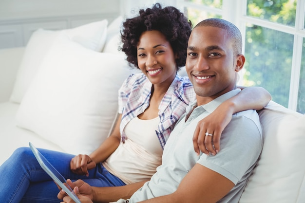 Happy couple using tablet on the sofa in the living room