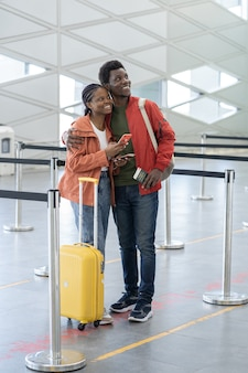 Happy couple waits for plane in airport terminal