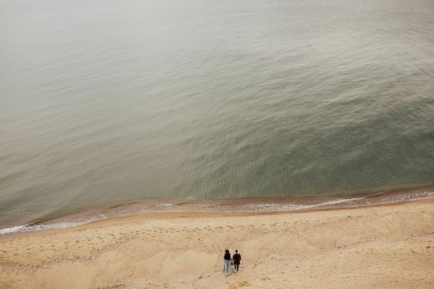 遠くからビーチに沿って歩く幸せなカップル。