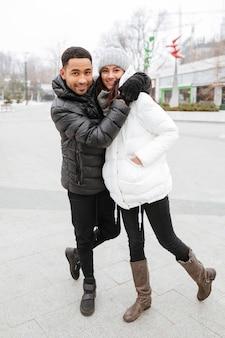 幸せなカップルのウォーキングと冬の公園でのenbracing
