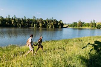 Happy couple walking in green grass near the idyllic lake