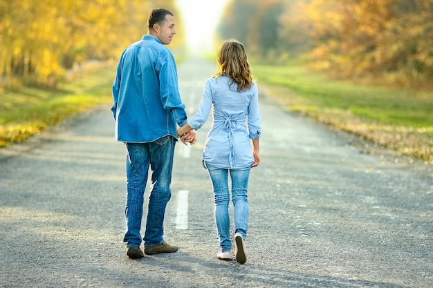Happy couple walking on the road in nature in the park travel
