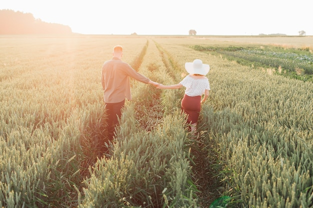 Happy couple walks in fields on summer evening ,holding hands. they are going to happy future . love and happiness.mutual understanding. happy moments of life. tenderness and trust. lifestyle.