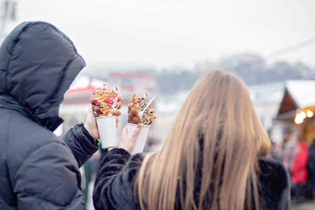 Happy couple in warm clothes in love eating bubble waffles at christmas fair. holidays, winter, christmas and people