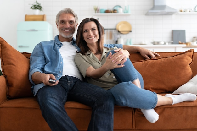 自宅のソファに座ってテレビで映画を見ている幸せなカップル。