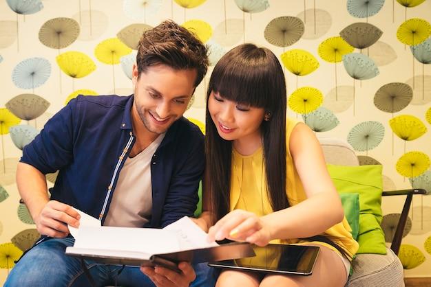 バーでノートブックでソーシャルメディアを見ている幸せなカップル。彼らは勉強しているか働いています。