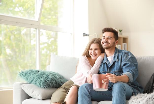 家でテレビを見ている幸せなカップル