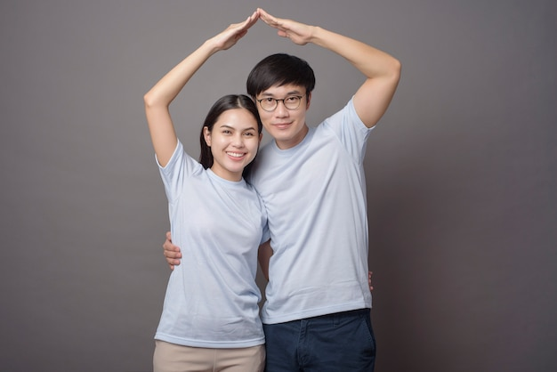 A happy couple wearing blue shirt is making armsroof in grey