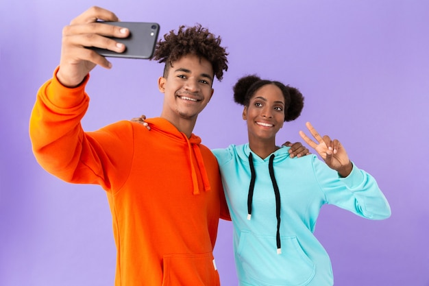 Happy couple wearing colorful sweatshirts taking selfie on smartphone, isolated over violet wall