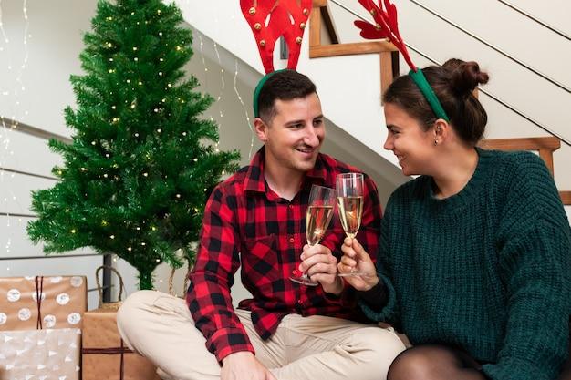 一緒にクリスマスを祝うシャンパンとトナカイの角トーストを身に着けている幸せなカップル休日