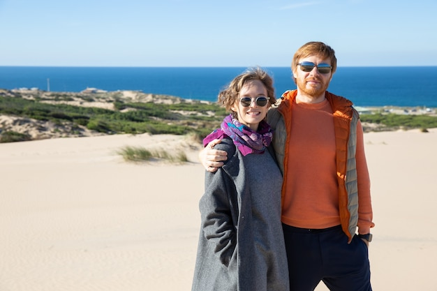 Happy couple wearing warm clothes, spending leisure time at sea, standing on sand, hugging, looking at front