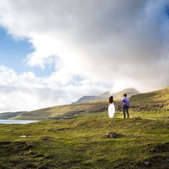 A happy couple in wedding dresses or the bride and groom holding hands and looking at nature. faroe islands