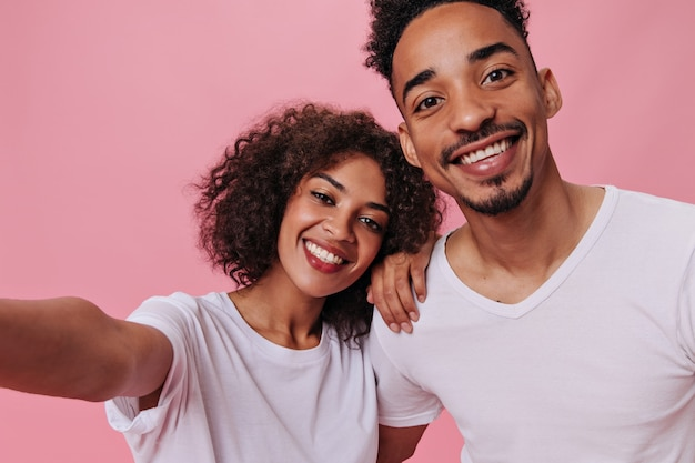 Happy couple in white t-shirts taking selfie on pink wall
