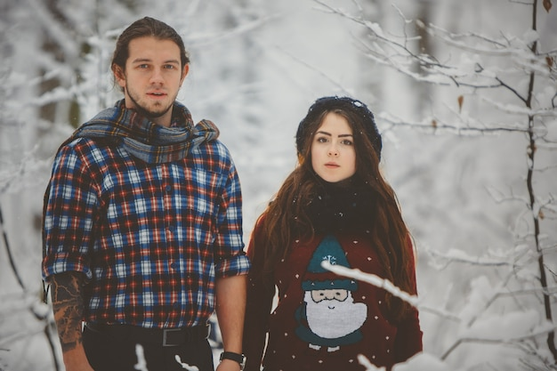 Happy couple in winter clothes walking outdoors in park