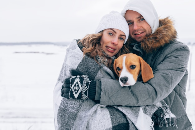 Happy couple at the winter landscape happy family with beagle dog. winter season