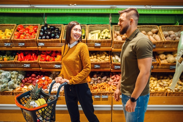 Happy couple with basket in grocery store together