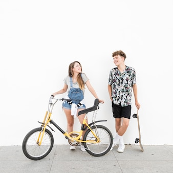 Happy couple with bicycle and skateboard looking at each other