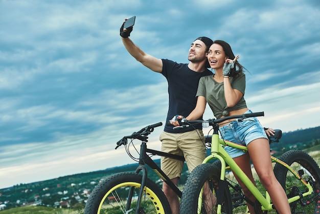 야외에서 스마트폰으로 셀카를 찍는 자전거와 함께 행복한 커플