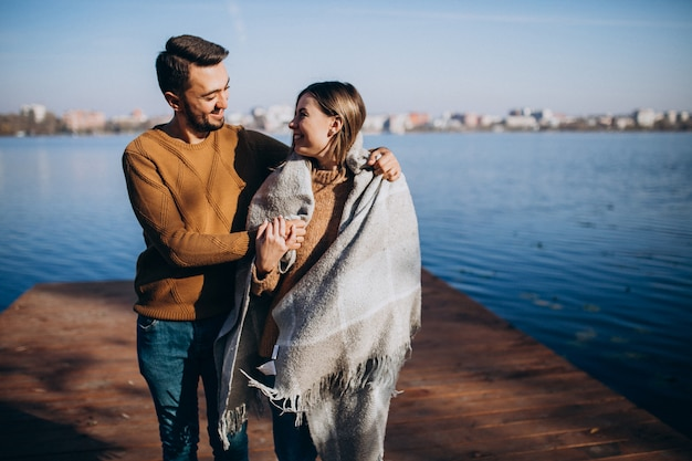 Happy couple with blanket by the river