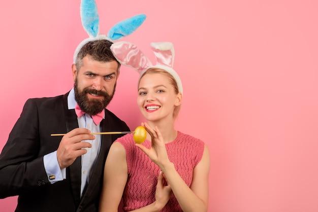 Счастливая пара с кроличьими ушами крася яйца на пасху. украшение яиц. семья празднует пасху.