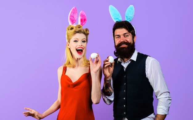 Happy couple with bunny ears with white eggs for easter, funny family, spring holidays.