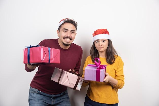 白い壁の上のクリスマスプレゼントと幸せなカップル。