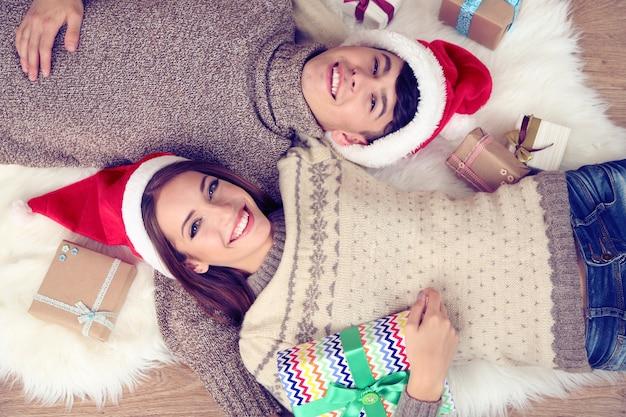 Счастливая пара с рождественскими подарками, отдыхая дома