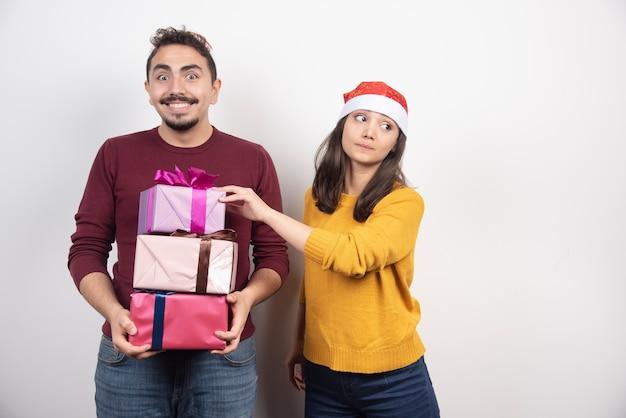 Coppia felice con regali di natale su un muro bianco.