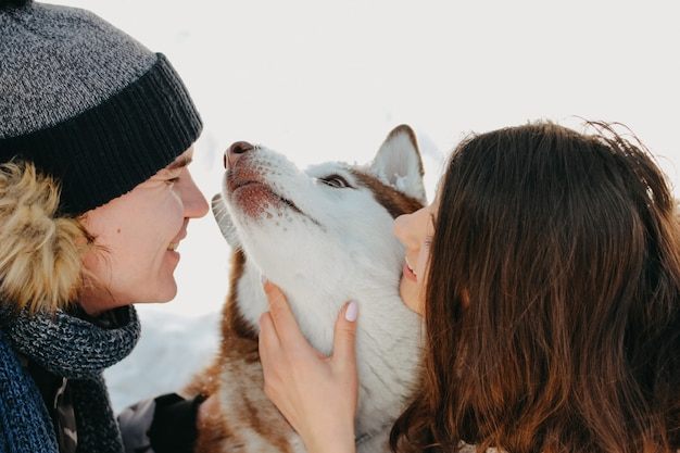 The happy couple with dog haski at forest nature park in cold season. travel adventure love story