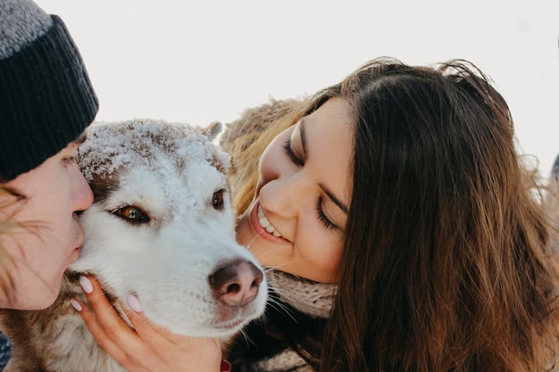 The happy couple with dog haski at forest nature park in the cold season. travel adventure love story