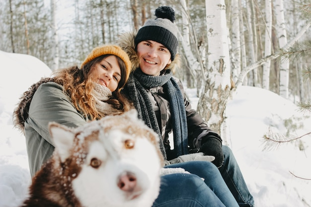 Happy couple with dog haski at forest nature park in cold season.