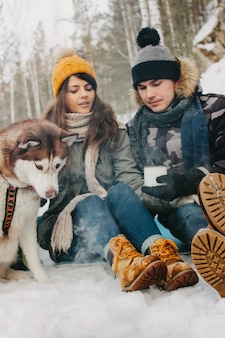 Happy couple with dog haski at the forest nature park in cold season.