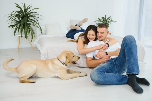 リビングルームで犬と幸せなカップル