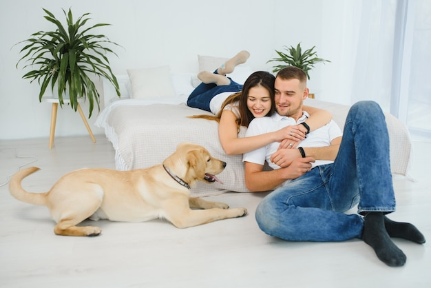 Happy couple with dog in living room
