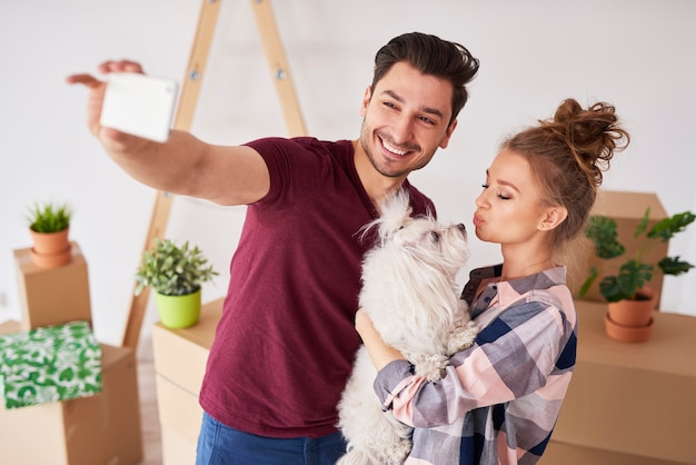 Счастливая пара с собакой, делающей селфи в новом доме