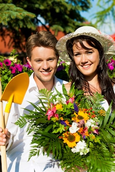 Happy couple with flower bouquet and gardening tools posing in garden