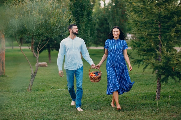 Happy couple with fruits in picnic basket walking in the park.