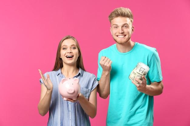 ドル紙幣と貯金箱の色の完全な jar ファイルと幸せなカップル