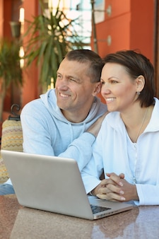 Счастливая пара с ноутбуком за столом