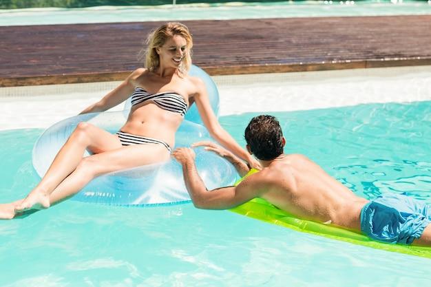 화창한 날에 수영장에서 lilos와 함께 행복 한 커플