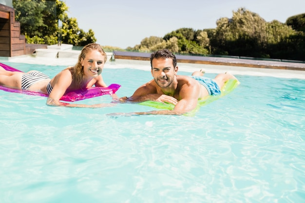 Happy couple with lilos in the pool in a sunny day