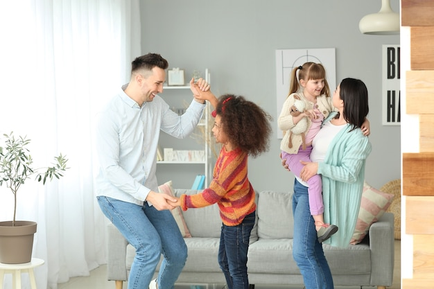 養子縁組の子供が家で踊っている幸せなカップル