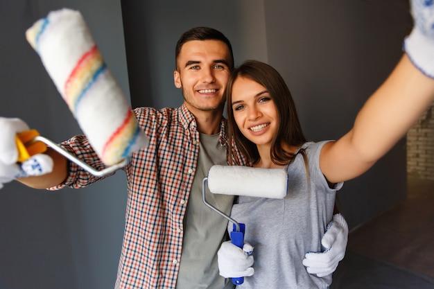 Счастливая пара с валиком, делая селфи фото на серую стену
