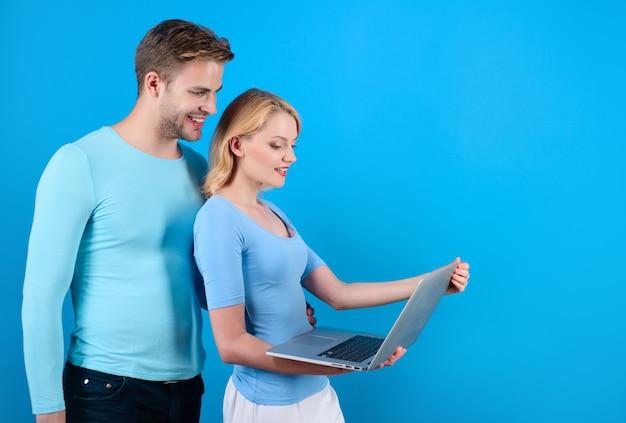 Счастливая пара с персональным компьютером женщина держит планшетный компьютер моды современные технологии и