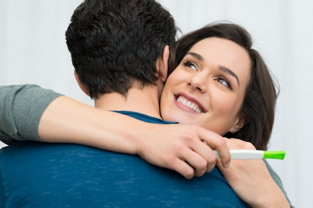 Happy couple with a pregnancy test