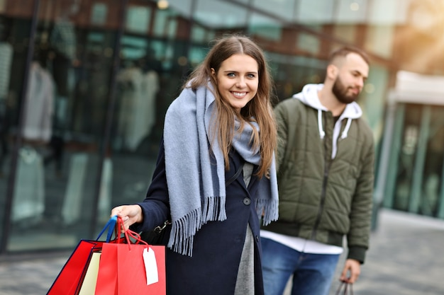 Happy couple with shopping bags after shopping in city smiling and hugging