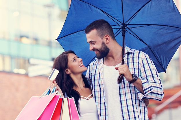 Happy couple with shopping bags after shopping in city
