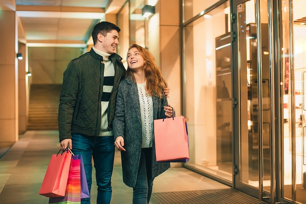 Happy couple with shopping bags enjoying night at city
